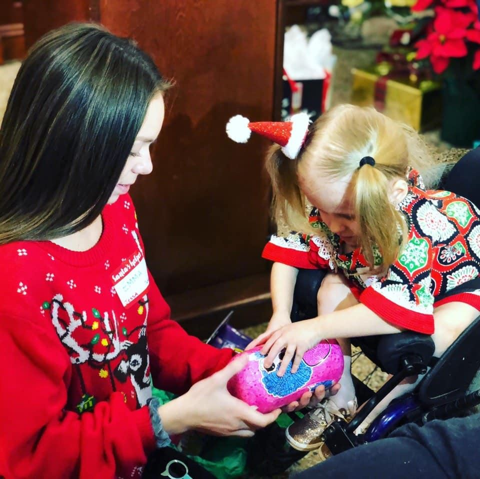 A CATA student helps a child at the Chance to Dance holiday party.