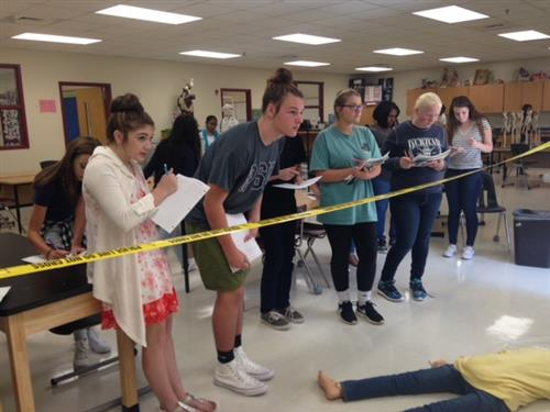 Students examine a staged crime scene.