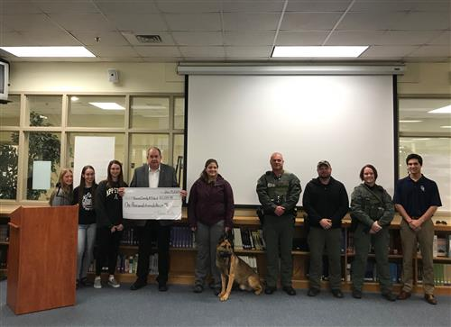 Members of the CATA Canine Club present the Sheriff with a check.