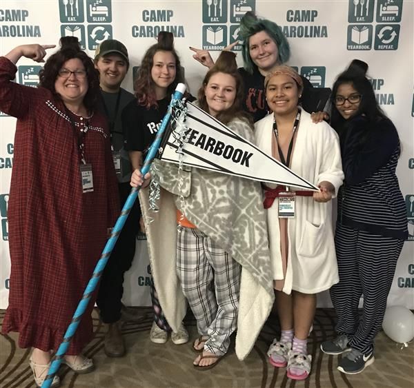 Yearbook students pose with spirit stick at camp