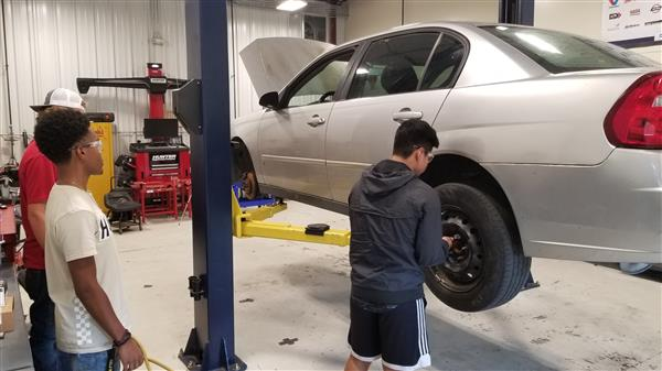 FHHS automotive students work on a car in partnership with UC shelter.