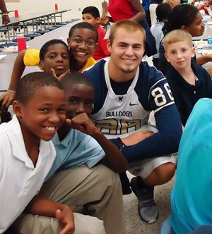 wingate football player with students