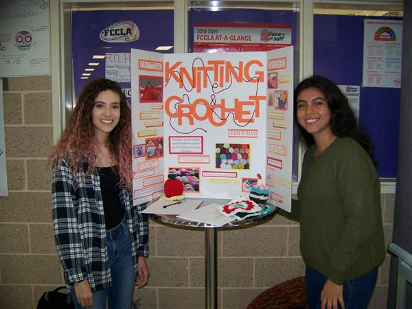 Students stand by Knitting and Crocheting Club display
