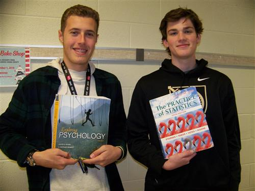 Students holding their college textbooks that are used in their online college classes.