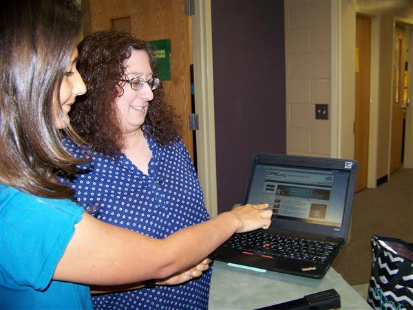 Student looks at CFNC website with counselor.
