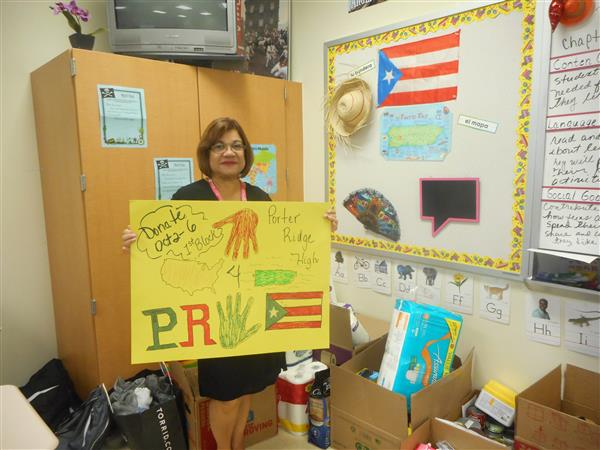 Spanish teacher Maria Koonce holds sign by items collected.