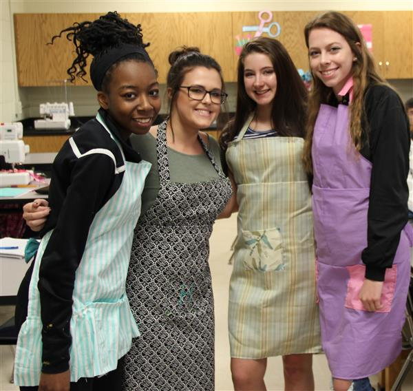 Girls modeling the aprons they made in class