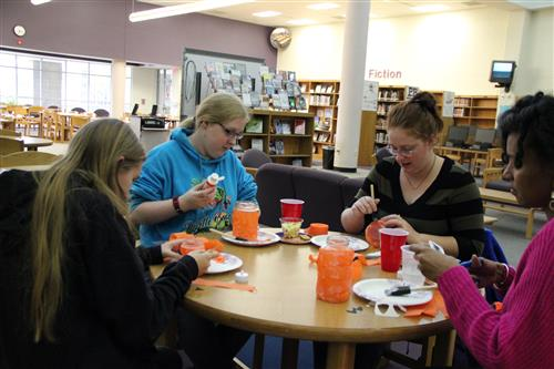 Students and a teacher work on Spooky Jars at the October Maker Series event.