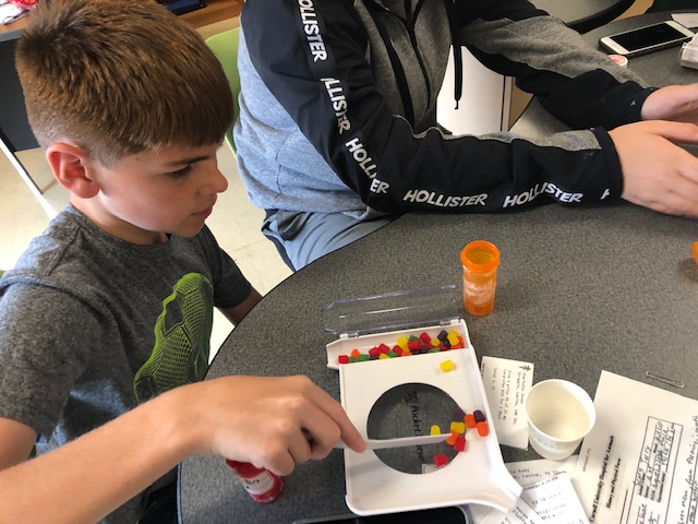 Camp participants learn to count out prescriptions using candy.