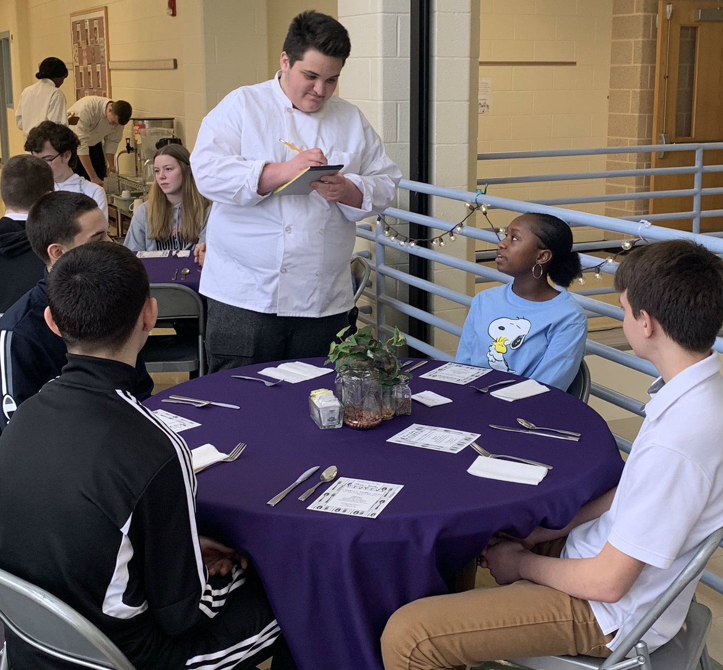 Culinary student takes food orders during Manners Meal.