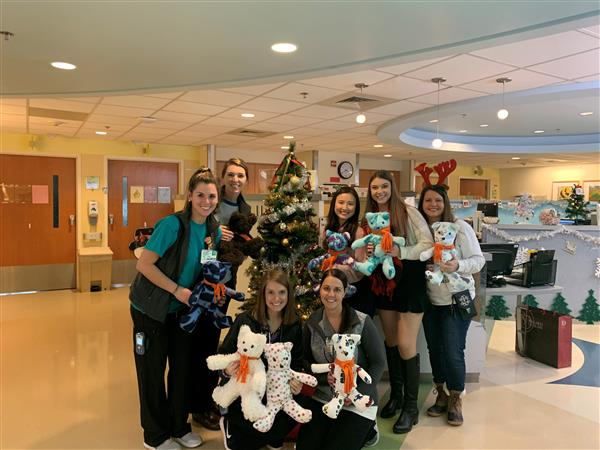 Sierra poses with hospital staff and bears.