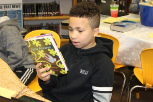 Student reading book during book tasting