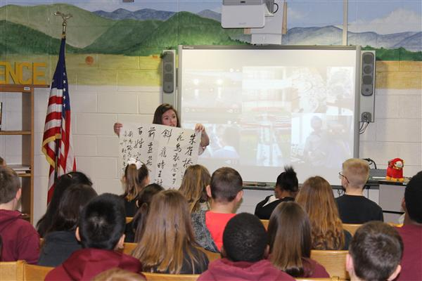 Mrs. Kriska displays poster with Chinese characters