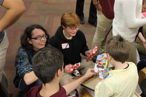 Beta students help elementary students unwrap gifts