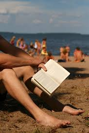 Picture of man holding book on the beach