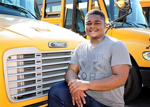 Xavier Huntley in front of school bus